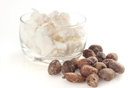mantequilla: karité nueces cerca de mantequilla, aisladas sobre fondo blanco