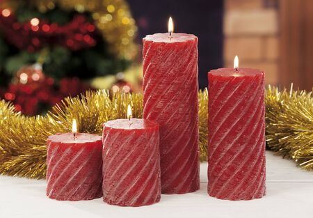 Closeup of red Christmas candles on colored and out of focus background