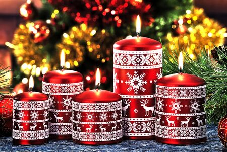 Closeup of Christmas candles on colored and out of focus background Stock Photo
