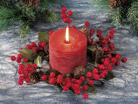 Closeup of red Christmas candle on colored background