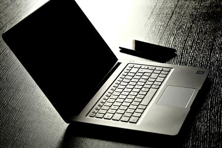 smartphone near laptop on office table