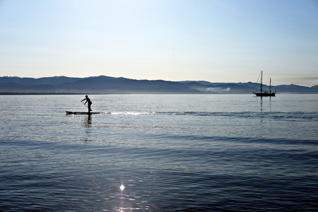 seascape with sailboat and man on stand up paddle