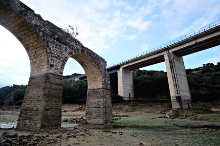old ruined bridge and modern overpass