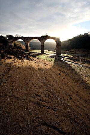 old ruined bridge over dry river Banco de Imagens