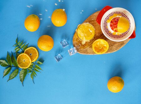 Glass of fresh juice with oranges placed on wooden boards. Blue background. Concept of healthy drinks, antioxidants . Juice and ice splashes .