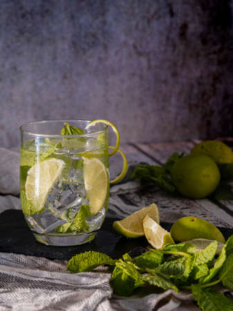 Mojito cocktail with lime and mint in a glass glass on a gray stone base.