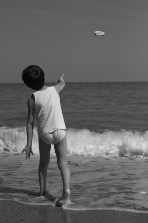 child on the beach throw a stone in the sea photo