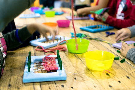 Educational weaving and knitting activity. Knitting wool for kids. Stock Photo