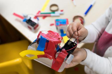 Robô do lixo, atividade STEAM para estudantes, caixa plástica com tiras de papel, motor DC e duas pilhas AA, fitas coloridas. Mexer e fazer, atividades educativas para escolas e crianças Foto de archivo