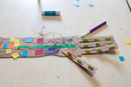 A cardboard arm with 4 fingers decorated. A cardboard arm that simulates a robot arm for kids in STEAM workshop. Robot arm, tinkering for children