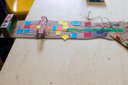 Een kartonarm met 4 vingers versierd. Een kartonarm die een robotarm voor kinderen in de STEAM-workshop simuleert