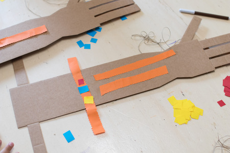 tinkering: A cardboard arm with 4 fingers decorated with orange strips of paper. Education robotic hand for kids Stock Photo