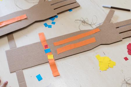 Een kartonnen arm met 4 vingers versierd met oranje stroken papier. Onderwijs robothand voor kinderen Stockfoto