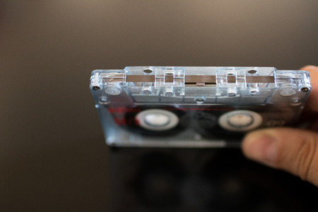 Hand holds an old audio cassette. Check integrity of magnetic tape. Audio tools from 80s