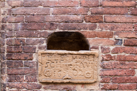 Detail of an ancient Latin-style inscription embedded in a red brick wall