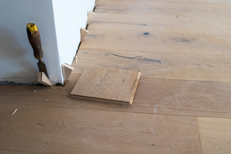 Oak colored parquet during installation on an old stoneware floor near an open window. Grazing light in the morning during the renovation of an apartment
