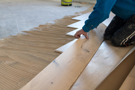 Renovation of an apartment, skilled worker uses a plastic hammer when installing pre-finished interlocking parquet. Laying with brown glue on an existing floor. Installation of oak colored parquet