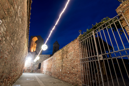 Ancient gate of a medieval cloister in an ancient town in central Italy. Brick walls of a medieval courtyard with an iron gate. Medieval night scene with tower in background and mystic lights trail
