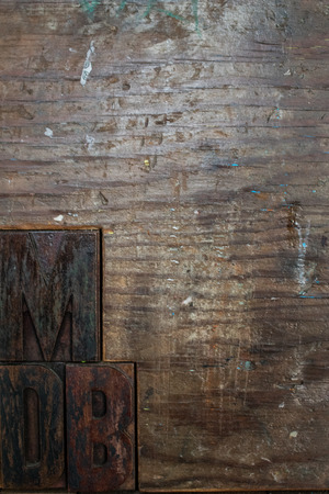 typographic characters depicting black M D B letters made of wood and embedded in a wooden wall. stamps placed on a wooden wall. 免版税图像
