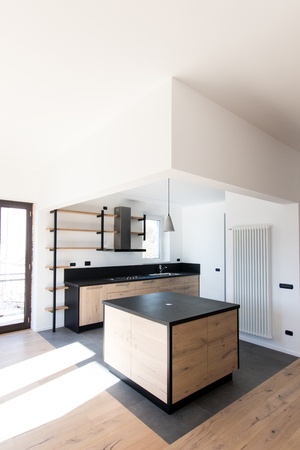 New kitchen in oak and black granite and stainless steel with island, sink, doors, shelves and extractor hood. Industrial design cuisine in a renovated apartment with gray concrete flooring. Cookery