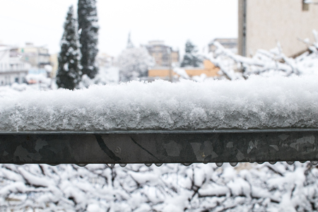 Snow on the handrail of an iron railing. Cold ice and snow in winter in the city, effects of climate change with low-altitude snow.