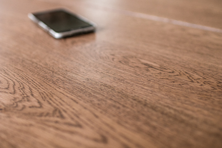 wooden meeting table with blurred smartphone in the background. Business activity in the morning