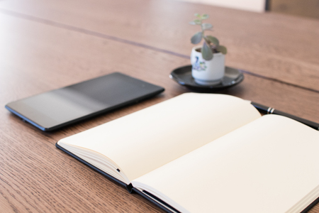 Notebook, tablet and pen on a wooden table. Work space for a journalist or blogger. Journalism activities online via social media and notebook. Analog and digital together