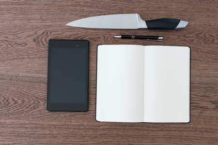 Tablet, notebook, pen and a knife on a wooden table. Violence against journalism, fake news and murders of journalists for press silence. Concept for hoaxes and repression of freedom of the press