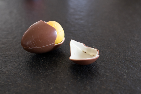 Easter egg for children with yellow surprise inside. Chocolate egg on a black table, easter gift for children. Broken milk and white chocolate egg with children's surprise 免版税图像