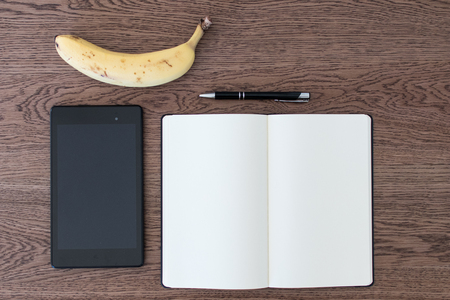 Tablet, notebook, pen and a banana on a wooden table. Image concept for journalism, liar and fake news, problems of hoaxes and truthfulness of the sources. data analysis of qualified journalism 免版税图像