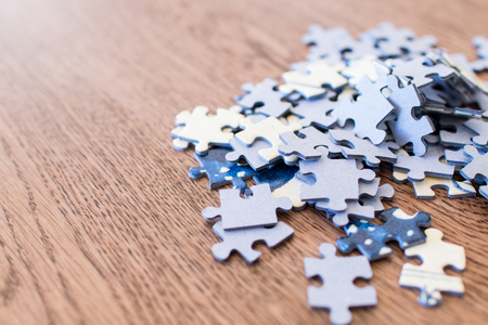 blue tiles of a puzzle on a wooden table. Concept to indicate leadership, influencer, vision and a solution to complex problems. Some tiles are organized in 3D form up to top