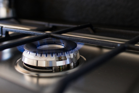 Gas cooker with lit blue flame. Example of supplies for home appliances of a modern kitchen. Image for gas supplies or kitchen items like stove or flame burner 免版税图像