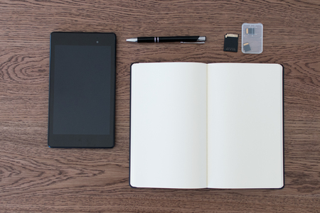 Tablet, notebook, pen and SD cards. Setup of a workspace for a journalist and blogger. Image for journalism, data analyst, blogger and influencer. Online communication and social media, words and pics 免版税图像