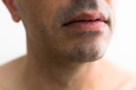 mouth of a man with a shaved beard. detail of the lips in the foreground with blurred white background. lower part of a white man's face