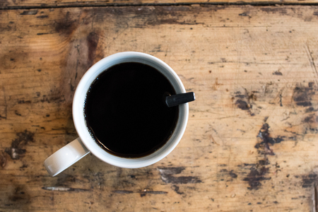 white cup of black coffee with teaspoon on a rough wooden table with veins. Work table with coffee cup 免版税图像