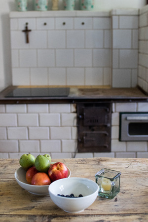 fruit bowl with apples and pears and  bowl with blueberries on a rough wooden table with dark veins and a candle close up. Two breakfast dishes on a table with crucifex on background. convent breakfast