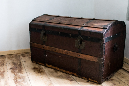dark wood trunk in a country house. antique treasure chest with metal hinges to store clothes and materials