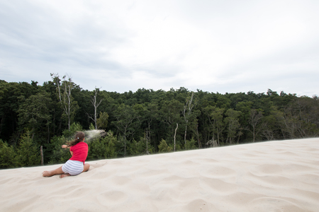 Little girl playing on her back sitting on the sand with red sweater and in the background a forest. Coniferous forest near sandbanks on the Baltic Sea