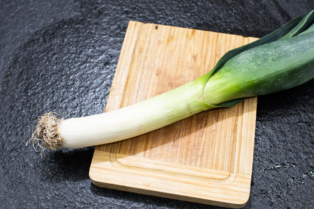 leek ready to be cut and cooked. Leek on a wooden cutting board and on a black table ready to be used in a winter recipe