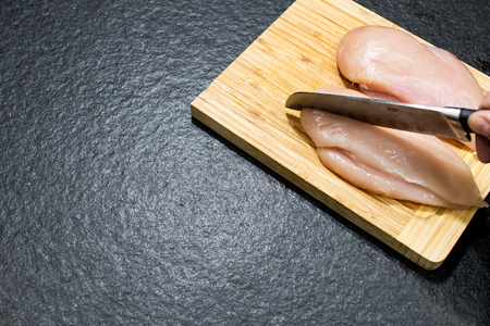chicken breast divided in half on a wooden cutting board. Chicken to cook in light recipes for a diet. Whole chicken breasts to be cut