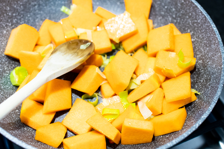 Pumpkin and leek cubes are cooked and sautéed in a non-stick pan on the stove. Cook a recipe with pumpkin and leek, pour the pumpkin into the pan
