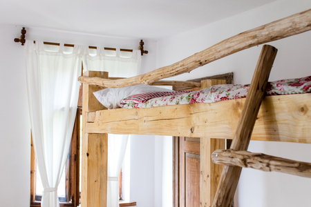 details of the interior of a bedroom of an old country house built with rough wood.