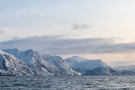 Arctic landscape in winter with snowy mountains and sea. Norwegian coasts and fjords seen from the boat in the open sea. Arctic polar north europe landscape with white snow and ice 免版税图像 - 141794183