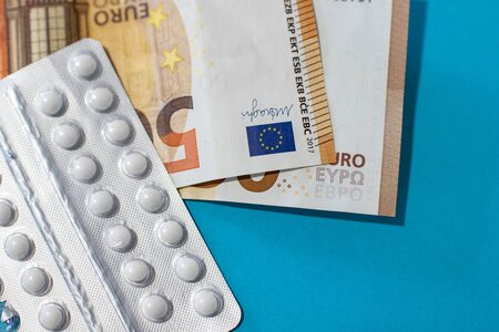 Pills blister on money euro banknotes for pharmaceutical cost. Rising prices of healthcare system. Medical on blue background. Increased costs for coronavirus pandemic. Vaccine and antibiotic 免版税图像 - 143693020
