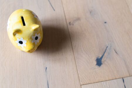 yellow piggy bank on a oak wooden floor parquet  background. Saving money. Finance and savings economy. Building renovation and energy saving