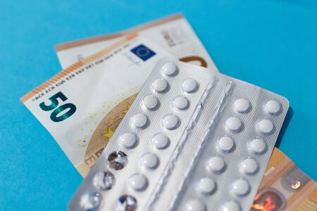 Pills blister on money euro banknotes for pharmaceutical cost. Rising prices of healthcare system. Medical on blue background. Increased costs for coronavirus pandemic. Vaccine and antibiotic 免版税图像