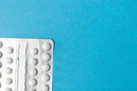 Pills blister on blue background, medicine cost for healtcare system. Pharmacy, drug modern concept. Round Pills in pack background. Package for pharmacy and medicine background. Hospital treatment