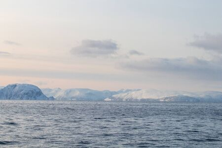 Arctic landscape in winter with snowy mountains and sea. Norwegian coasts and fjords seen from the boat in the open sea. Arctic polar north europe landscape with white snow and ice 免版税图像