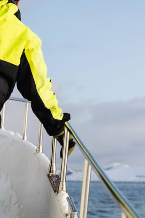 Sailor in the north arctic sea with snow and ice leaning and supporting on a metal handrail wearing a phosphorescent yellow and black jacket. Emergency jacket and sailor on a boat 免版税图像 - 141797431