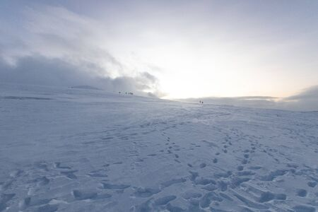 Polar landscape with snow and wind in the mountains. Hiking and snow hiking in the mountains with footprints on the ice and snow. Adventure and excursions in the cold in winter